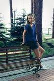 Jonge vrouw die zich dichtbij bank in park, het wachten bevinden Royalty-vrije Stock Afbeelding