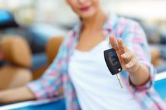 Jonge vrouw die zich dichtbij convertibel met in hand sleutels bevinden Stock Foto