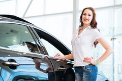 Jonge vrouw die zich dichtbij een auto bevinden Stock Fotografie