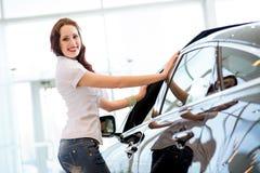 Jonge vrouw die zich dichtbij een auto bevinden Stock Foto