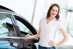 Jonge vrouw die zich dichtbij een auto bevinden Stock Afbeeldingen