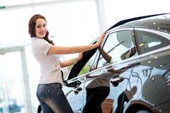 Jonge vrouw die zich dichtbij een auto bevinden Stock Foto's