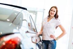 Jonge vrouw die zich dichtbij een auto bevindt Stock Afbeeldingen