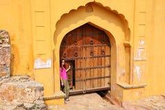 Jonge vrouw die zich door de poort in Amber Fort dichtbij Jaipur, Radja bevinden stock foto