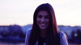 Jonge vrouw die zich door een rivier in stad bij schemer, het lachen bevindt stock videobeelden