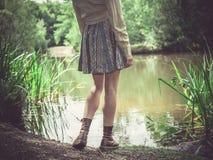 Jonge vrouw die zich door vijver in bos bevinden Stock Afbeeldingen