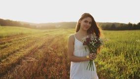 Jonge vrouw die zich in een weide met boeket van wilde bloemen op de zomeravond bevinden stock video