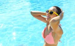 Jonge vrouw die zich in een zwembad bevindt Royalty-vrije Stock Foto's