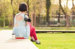 Jonge vrouw die zich met rug bevinden en oortelefoons houden stock afbeeldingen