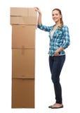 Jonge vrouw die zich naast toren van dozen bevinden Royalty-vrije Stock Afbeeldingen