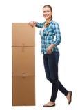 Jonge vrouw die zich naast toren van dozen bevinden Stock Foto's