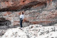 Jonge vrouw die zich onder klip bevinden Reiziger en blogger stock afbeeldingen