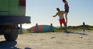 Jonge vrouw die zich op concrete post bij strand 4k bevinden stock video