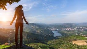 Jonge vrouw die zich op de rand van een klip bevinden die de Douro-Vallei bekijken Royalty-vrije Stock Afbeelding