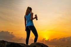 Jonge vrouw die zich op de rotsen door het overzees bevinden, fles houden en op de zonsopgang op een tropisch eiland letten Stock Afbeeldingen