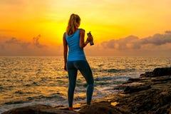 Jonge vrouw die zich op de rotsen door het overzees bevinden, fles houden en op de zonsopgang op een tropisch eiland letten Stock Afbeelding