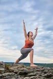 Jonge vrouw die zich op de steen en het praktizeren yoga dichtbij de grote rivier bevinden Stock Foto