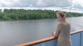 Jonge vrouw die zich op dek van cruiseschip bevinden en rivier en landschap bekijken stock video
