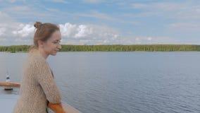 Jonge vrouw die zich op dek van cruiseschip bevinden en rivier en landschap bekijken stock videobeelden