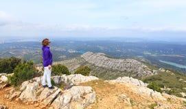 Jonge vrouw die zich op een berg bevinden en een vallei bekijken Royalty-vrije Stock Foto