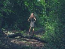 Jonge vrouw die zich op login het bos bevinden Royalty-vrije Stock Foto's