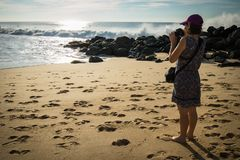 Jonge vrouw die zich op zandig strand die van Atlantische kust bevinden foto's van mooi zeegezicht en surfers nemen Stock Afbeelding