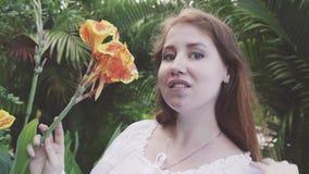 Jonge vrouw die zich in park en ruikende bloem bevinden stock videobeelden