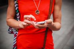 Jonge vrouw die zich in straat bevinden die haar telefoon met behulp van Stock Fotografie
