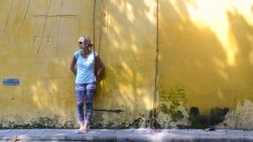 Jonge vrouw die zich voor de gele muur in Vietnam bevinden stock video