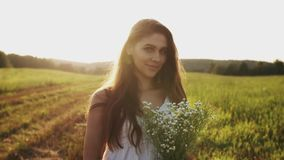 Jonge vrouw die zich in weide met boeket van wilde bloemen op de zomeravond bevinden Glimlach in camera stock video