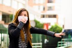 Jonge vrouw die zijn beschermend masker met haar hand op de straat in de stad met luchtvervuiling houden, die om een taxi vragen royalty-vrije stock foto's