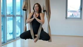 Jonge vrouw die zitting in hangmat voor yoga binnen mediteren stock videobeelden