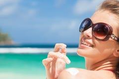 Jonge vrouw die in zonnebril zonroom op schouder zetten royalty-vrije stock foto