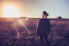 Jonge vrouw die zonsondergang op gebied met haar haar het blazen bekijken Stock Afbeeldingen