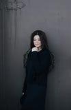 Jonge vrouw die zwarte kleren dragen die dichtbij poorten stellen Stock Foto's