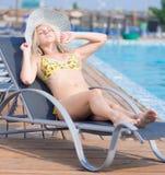 Jonge vrouw die in zwempak op chaise-longuepoolside leggen Stock Foto