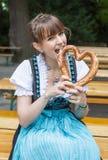 Jonge vrouw in dirndl met pretzel Stock Afbeelding
