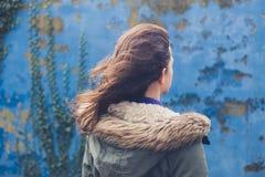 Jonge vrouw door blauwe muur op winderige dag Stock Foto's