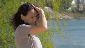 Jonge vrouw door de rivier Meisje bij het water met het ontwikkelen van haar Een de lente zonnige dag stock footage