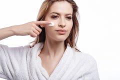 Jonge vrouw in een badjas die een room op haar gezicht, kuuroord en zorgportret, schoon natuurlijk gezicht, portret op een witte  Stock Foto