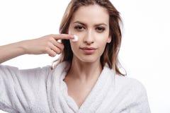 Jonge vrouw in een badjas die een room op haar gezicht, kuuroord en zorgportret, schoon natuurlijk gezicht, portret op een witte  Royalty-vrije Stock Foto's