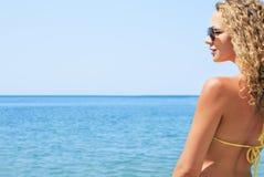 Jonge vrouw in een bikini die van de oceaanwinden genieten Stock Afbeeldingen
