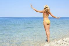 Jonge vrouw in een bikini die van de oceaanwinden genieten Royalty-vrije Stock Foto