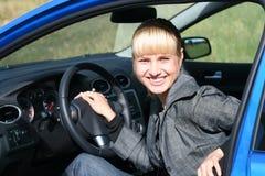 Jonge vrouw in een blauwe auto Royalty-vrije Stock Afbeeldingen
