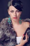 Jonge vrouw in een bontjas in oorringen Royalty-vrije Stock Foto's