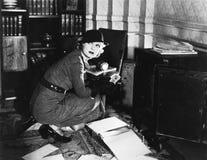 Jonge vrouw in een bureau naast een brandkast, die over haar schouder kijken (Alle afgeschilderde personen leven niet langer en g royalty-vrije stock foto