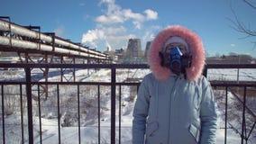 Jonge vrouw in een filtrerend beschermend masker op de achtergrond van rokende pijpen stock videobeelden
