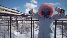 Jonge vrouw in een filtrerend beschermend masker op de achtergrond van rokende pijpen stock footage