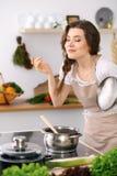 Jonge vrouw in een gestippelde biege schort kokende soep in de keuken stock fotografie