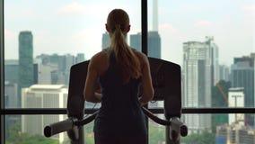 Jonge vrouw in een gymnastiek bovenop een wolkenkrabber opleiding op een renbaan met een mening over een gehele stad stock videobeelden
